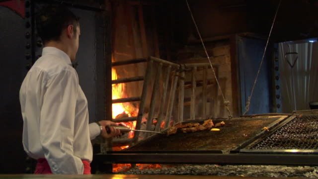 MS Rear view of man grilling meat in restaurant, Montevideo, Uruguay