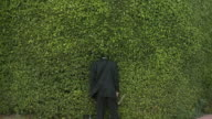 WS Rear view of man in full suit standing with head in hedge, holding clippers, South Beach, Florida, USA