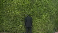 WS Rear view of man in full suit standing with head in hedge, South Beach, Florida, USA