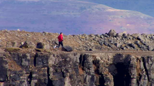 WS, TS, Rear view of man jogging in disused quarry, Wales, United Kingdom