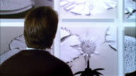 Rear view of man looking at panels of lily pads in gallery