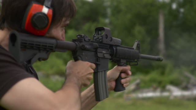 CU Rear view of man wearing ear protectors and firing M4 rifle, Stowe, Vermont, USA