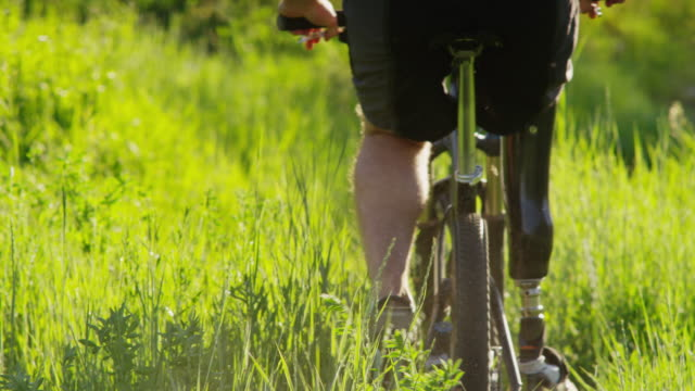 MS TU Rear view of man with artificial limb riding mountain bike through grassy hill / American Fork Canyon, Utah, USA