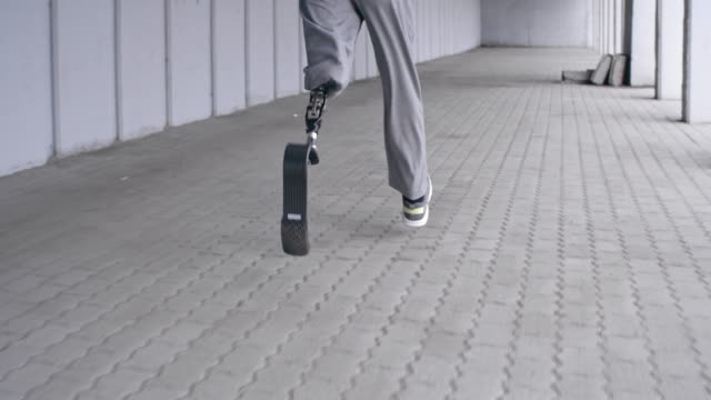 Rear view of man with prosthetic leg running outside