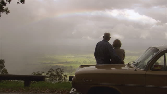 MS, Rear view of senior couple leaning against car bonnet and looking at view, Tamborine Mountain, Brisbane, Queensland, Australia