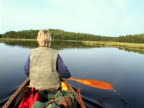 MS, PAN, Rear view of senior woman rowing in lake, Algonquin Provincial Park, Ontario, Canada