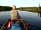 MS, Rear view of senior woman rowing in lake, Algonquin Provincial Park, Ontario, Canada