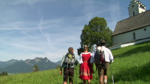 WS Rear view of three Bavarian people in traditional clothing hiking in Alpine landscape, Bavaria, Germany