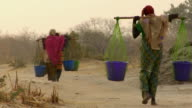 WS, Rear view of three women carrying water through arid area, Niamey, Niger