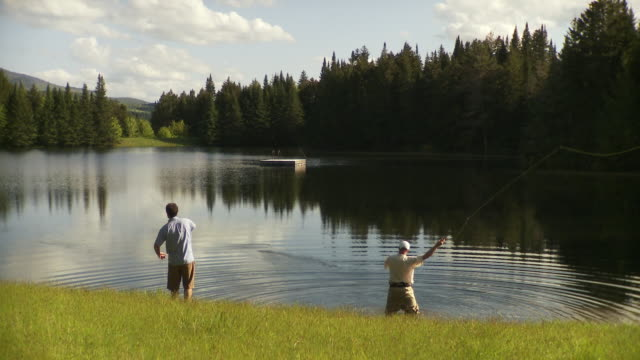 WS Rear view of two men fly fishing in scenics forest lake, Morristown, Vermont, USA