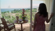 MS, PAN, Rear view of woman opening balcony, revealing table with champagne and flowers, Maui, Hawaii, USA
