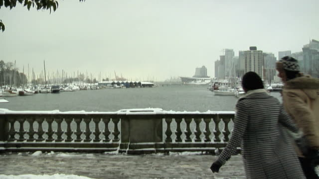 SLO MO WS Rear view of young couple walking on bridge in snow, boats in harbor and cityscape in background, Vancouver, British Columbia, Canada, PAN