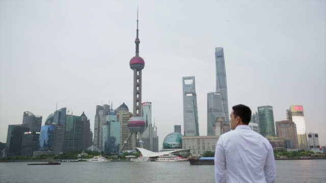 WS Rear View, Young man looking at Shanghai cityscape.