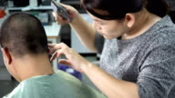 rear view: young woman barber try to cut tiny hair near his ear