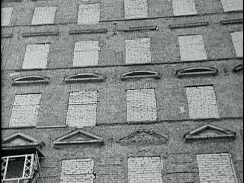 Rear windows building bricked in to prevent people escaping to West Berlin several memorial wreaths on ground by poles wrapped w/ barbed wire