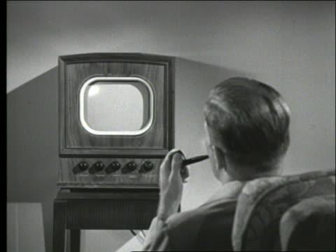 B/W rearview of man smoking pipe watching television / 1950's