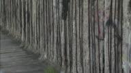 Rebar sticks through the graffiti covered Berlin Wall.