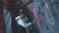 Rebellious African men drawing graffiti and man filming them on video camera