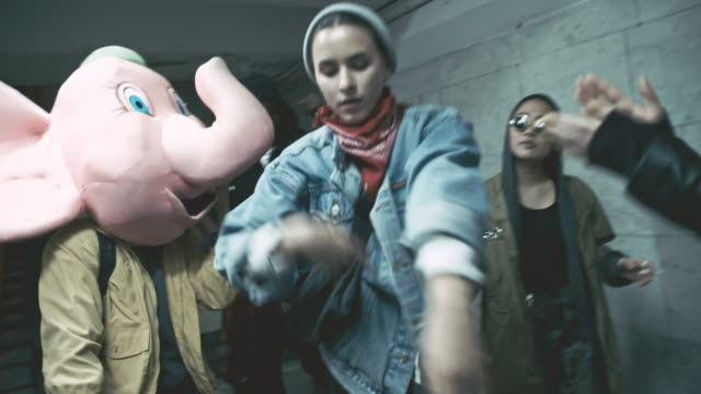 Rebellious group of friends dancing inside underground walkway