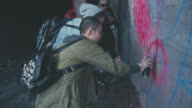 Rebellious young women drawing graffiti in tunnel