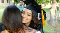 Recent college graduate excitedly hugs her mom after graduation ceremony