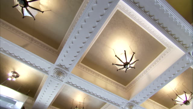Recessed lights illuminate a geometric ceiling in an art deco former London cinema. Available in HD.