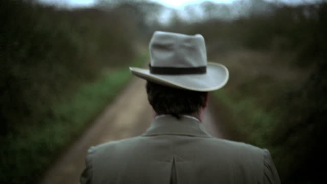 Reconstruction of a Detective Inspector walking along a country road to the body of a police man lying on the ground