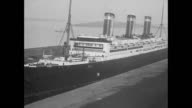 Record breaking transatlantic service ship the SS Leviathan comes into harbor and several dozen men run across the dock to meet it / men anchor the...