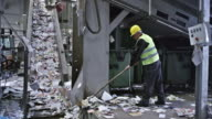 CS recycling facility worker sweeping paper onto conveyor belt