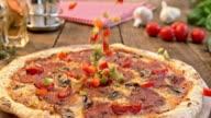 SLO MO rode en groene paprika's vallen op een pizza salami