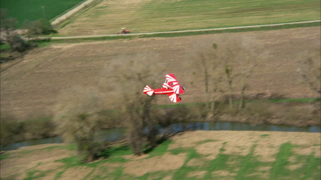 AIR TO AIR Red and white biplane flying over farmland