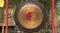 A red and yellow yin-yang decorates a gong. Available in HD.