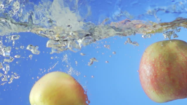 Red Apples Splashing Into Water (Super Slow Motion)