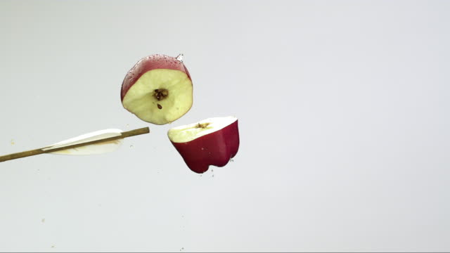 CU SLOW MO red arrow strikes and slices wet red apple in half on white background