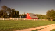 WS Red barn w/ white fence in front grassy field w/ dirt path trees power lines upper right gray/blue sky