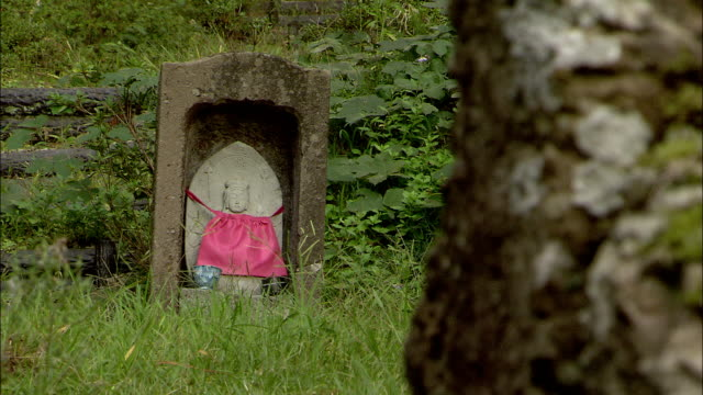 A red bib is attached to a shrine to the beloved deity, Jizo.