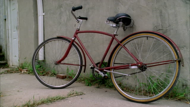 WS Red bicycle leaning against wall in unidentifiable area some grass weeds on concrete pavement Bike cycle