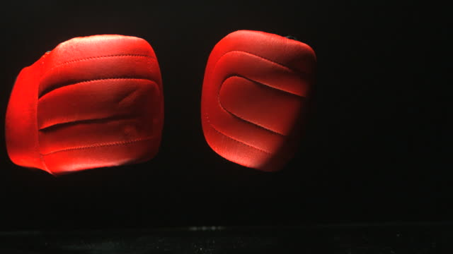 Red boxing gloves falling on black background