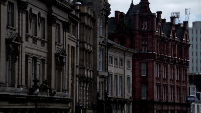 A red brick building contrasts with the white stone buildings surrounding it. Available in HD.