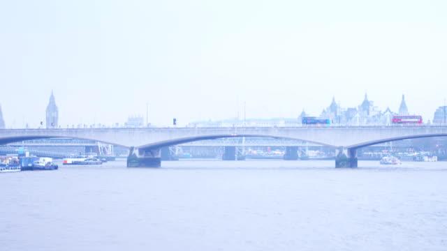Red bus goes over Waterloo bridge at river Thames overlooking Big Ben