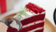 Red cake Strawberries cream cake on wooden dish on white table with human hand cutting , dolly shot right to left
