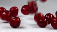 Red cherries falling onto table.