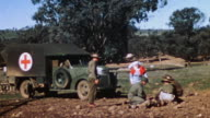 WS Red Cross nurse exiting ambulance and administering to downed US Marine trainee on obstacle course during WWII