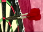 Red dart flies into black and white dartboard to score 180 board at angle against camera 2003 Embassy World Darts Championships Frimley Green Lakeside