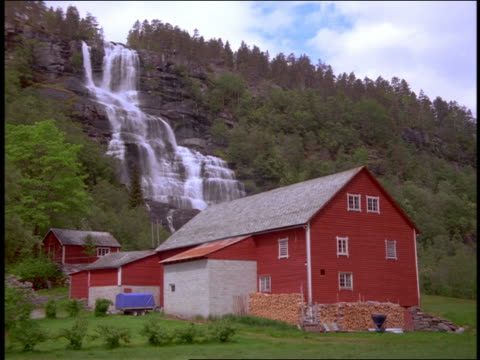 Red farm buildings + waterfall / Tvindefoss / near Voss, Norway