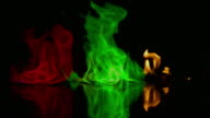 Red, green and yellow flames burning on black surface