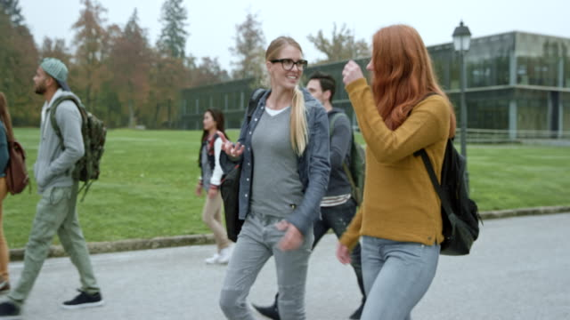 Red haired female student and her female friend talking as they walk on the campus on a fall morning