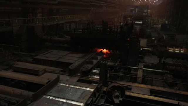 A red hot steel beam is shaped by machine as it moves along a rolling conveyor at the Evraz Plc Consolidated West Siberian Metallurgical Plant in...