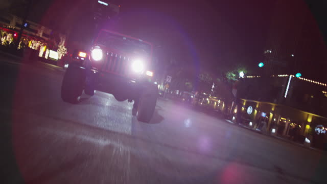 Red jeep drives down an urban boulevard at night; refractions from headlights hit the lens.