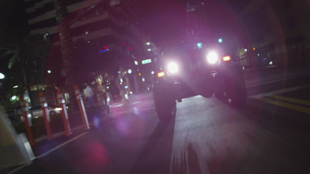 Red jeep drives down an urban boulevard at night.